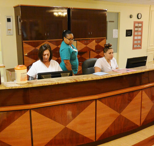 Skilled nurses behind wooden admissions desk at medical facility.