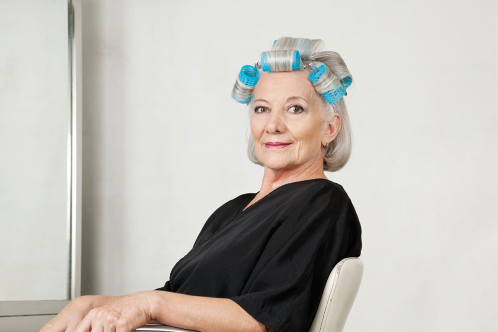 Portrait of senior female client with hair curlers at beauty salon