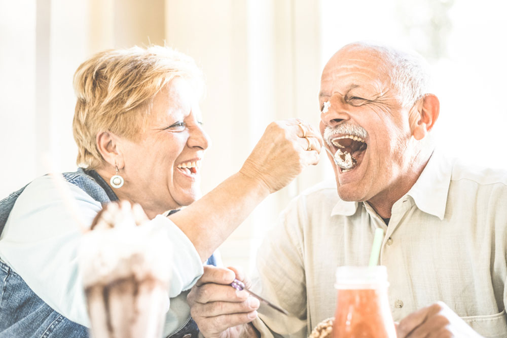 Happy retired senior couple in love enjoying bio icecream cup