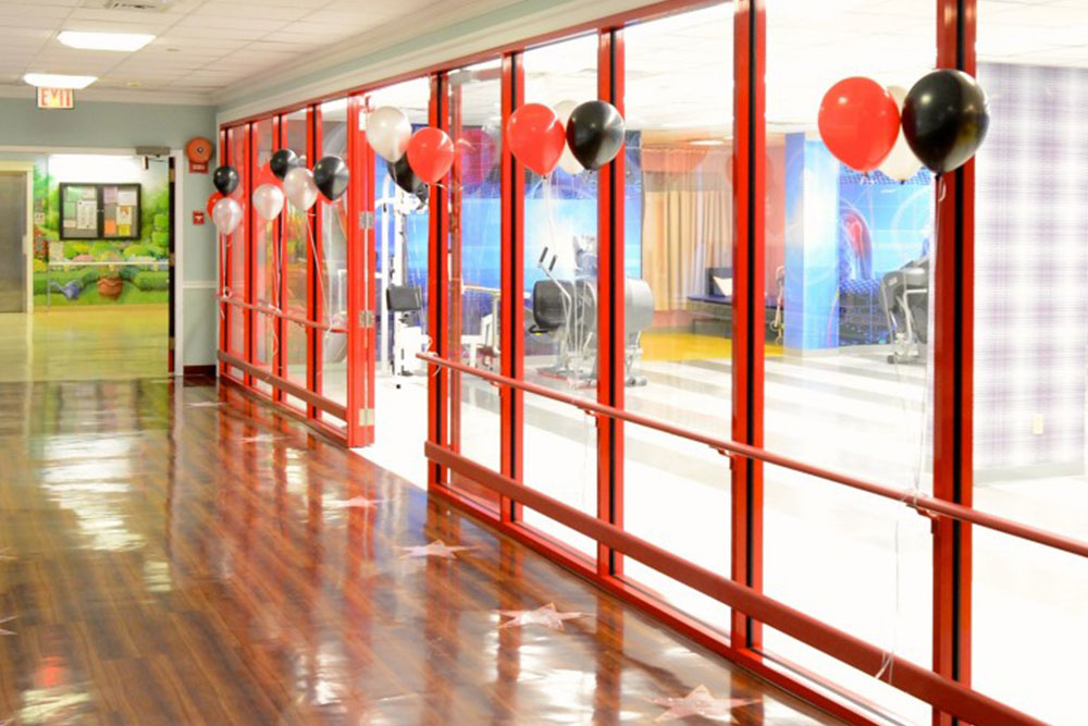 Hallway of East Neck Nursing Center filled with red, black, and white balloons.