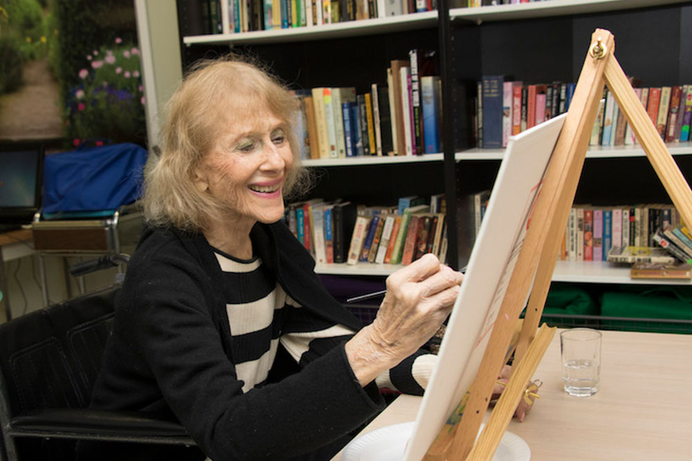 Senior woman smiling and painting at a desk easel.